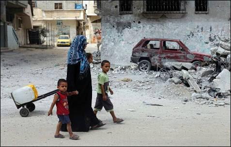 Una familia palestina camina junto a un coche dañadomientras regresa a su casa después de coger agua en una fuente públicaen Rafah, en el sur de la Franja de Gaza.