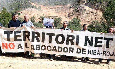 Pla general dels membres de les plataformes 'Almatret Net' i la 'Ribera Digna' en l'acció per denunciar el projecte de l'abocador de residus de Riba-roja i al fons les màquines que treballen en els terrenys. Imatge del 13 d'abril del 2019 (Horitzontal).