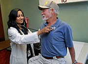 A doctor listens to a patient's heartbeat with a stethoscope.