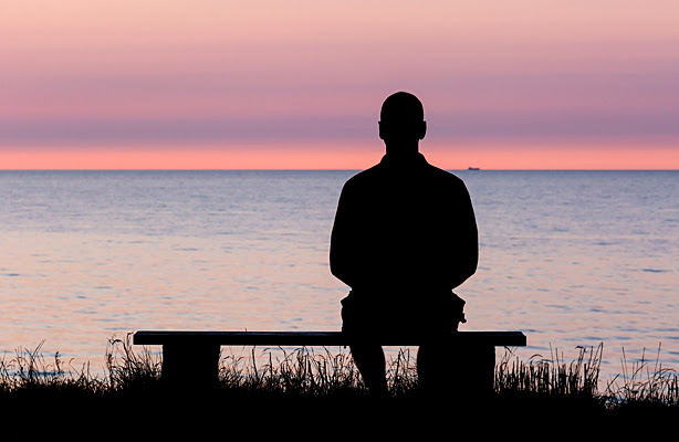A silhouette of a man sitting on a bench looking out at the water.