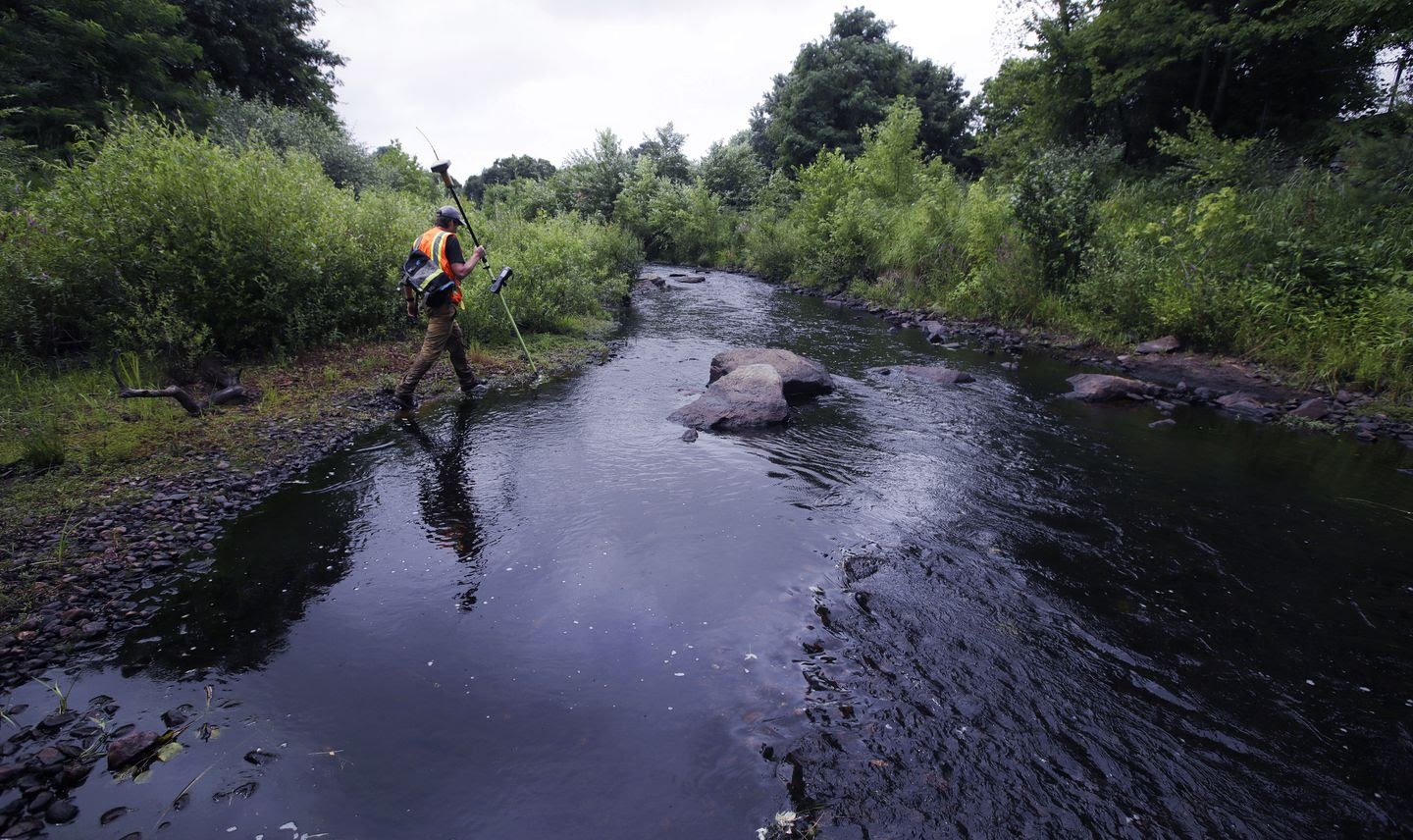 A surveyor walks the banks of the Mill River, at the site of the former Whittenton Pond Dam, just upstream from downtown Taunton, Mass., July 25, 2018.