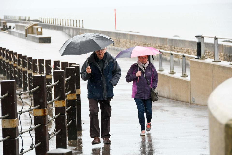 Visitors at the seaside resort of West Bay in Dorset were huddled under their umbrellas to dodge the heavy persistent rain on Wednesday