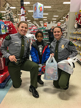Michigan Conservation Officers Anna Cullen and Jackie Miskovich shop with a child during the 2019 Shop with a Cop effort