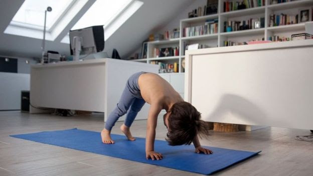 Menino faz ioga em casa