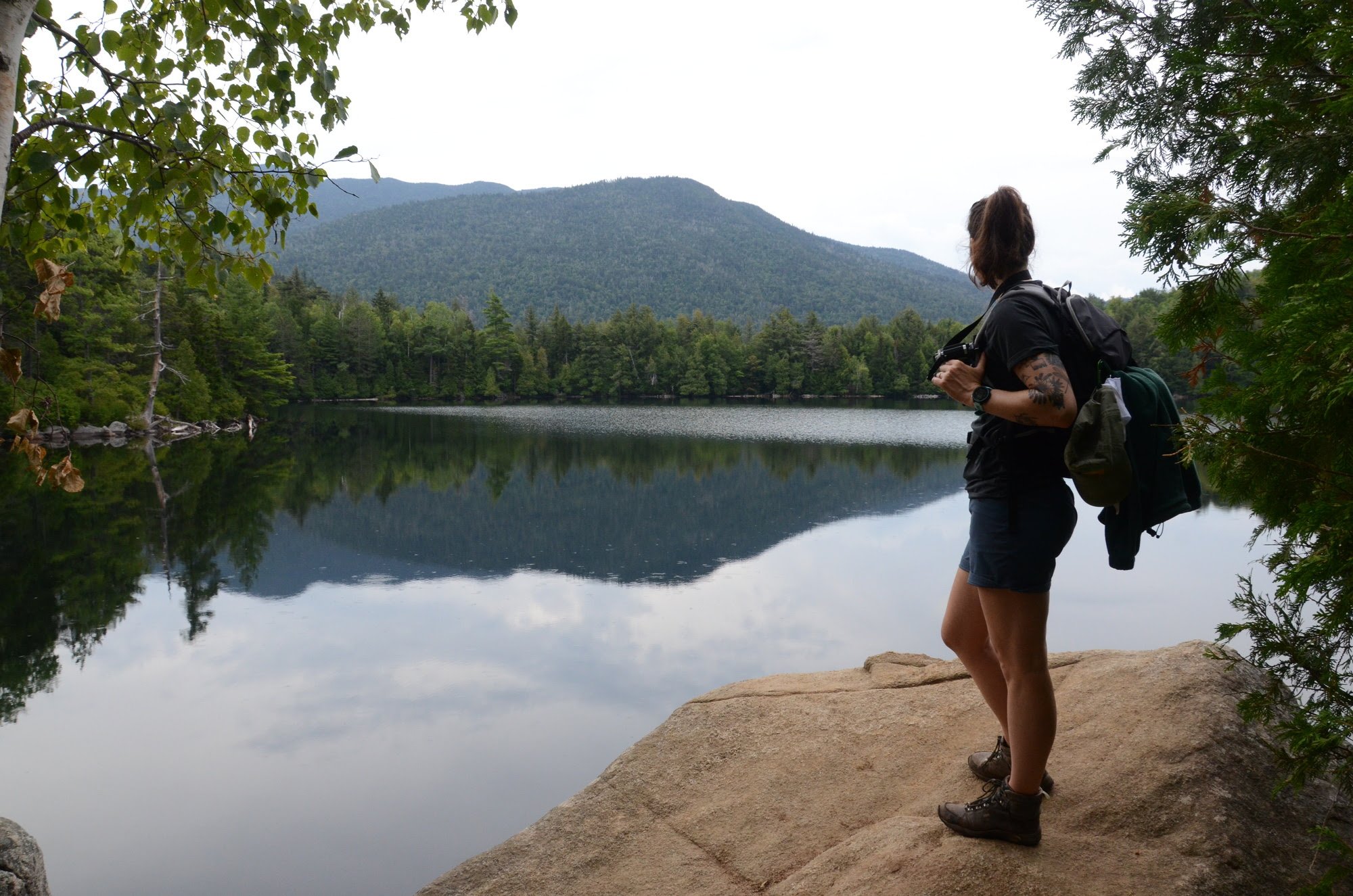 Hiker standing by pond