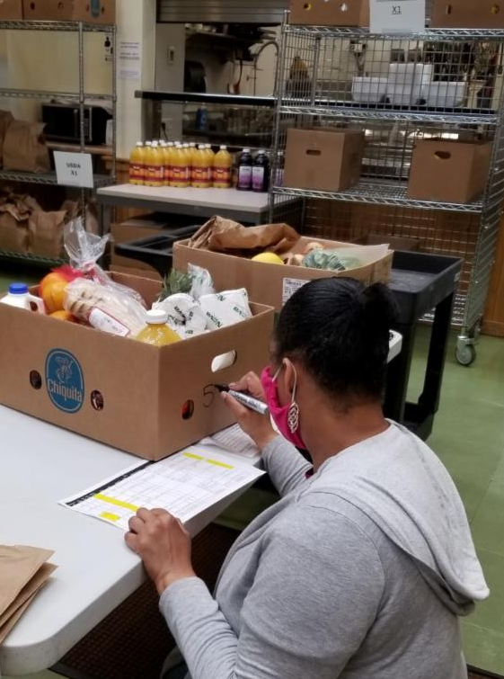 Volunteer writing on box of groceries