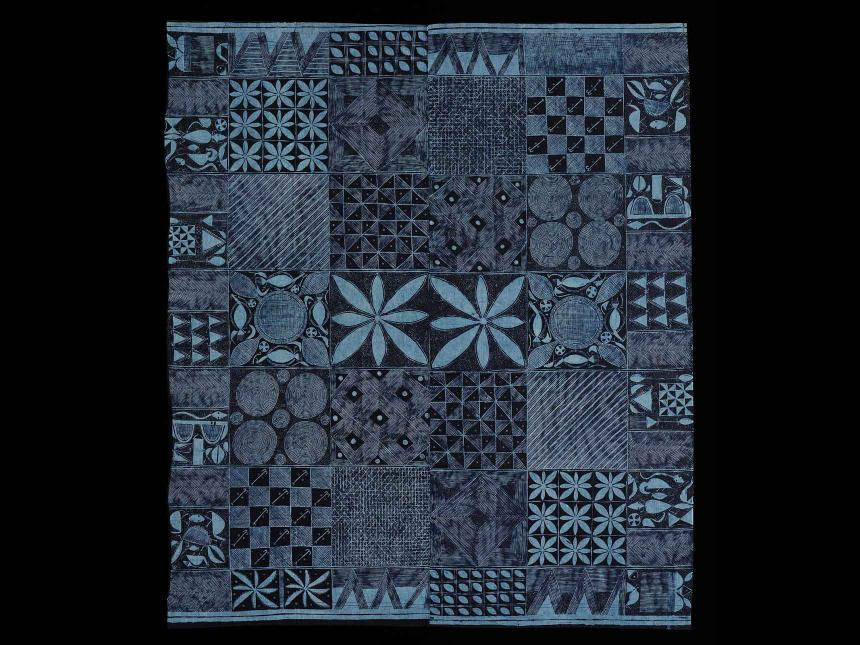 Image of a quilt made in shades of blue and black.
