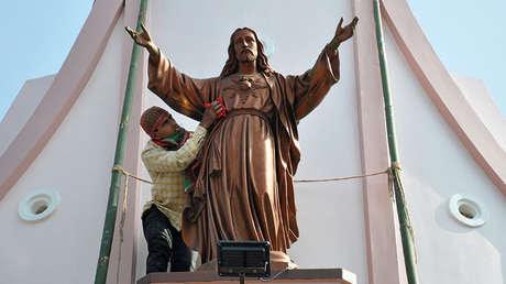 Un trabajador limpia una estatua de Jesucristo antes de las celebraciones de Navidad en las afueras de Agartala, India.