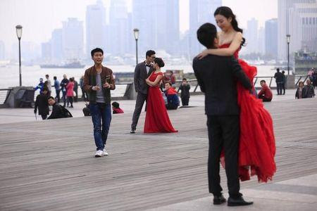 Couples prepare to have their photos taken on the Bund in Shanghai, China, November 3, 2015. REUTERS/Aly Song/Files