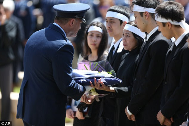 Maj. Gen. Michael E. Stencel presents a United States flag to the family of Ricky Best at Best's burial service with military honors at Willamette National Cemetery in Portland, Oregon on Monday. Best was one of two men killed May 26 during an attack on a Portland light-rail train