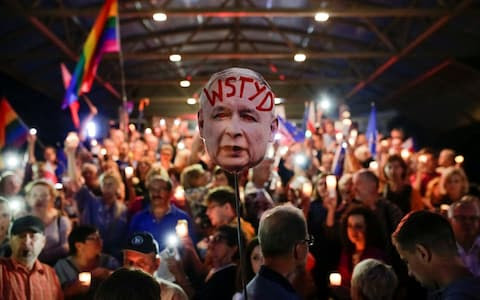 """Protestors in Krakow hold a sign that reads """"Shame"""", depicting Law and Justice party leader Jaroslaw Kaczynski"""