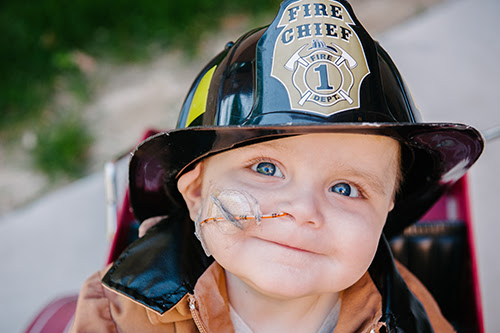 Image of a baby boy about two-years-old, smiling sweetly at the camera. The boy wears a fireman's hat and coat and we see that he's sitting in a play fire truck. An oxygen tube is taped to his cheek and leading into his right nostril.