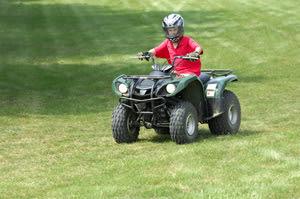Boy with a helmet riding an ATV