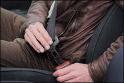 The figure above is a photograph showing a man about to buckle his seat belt.