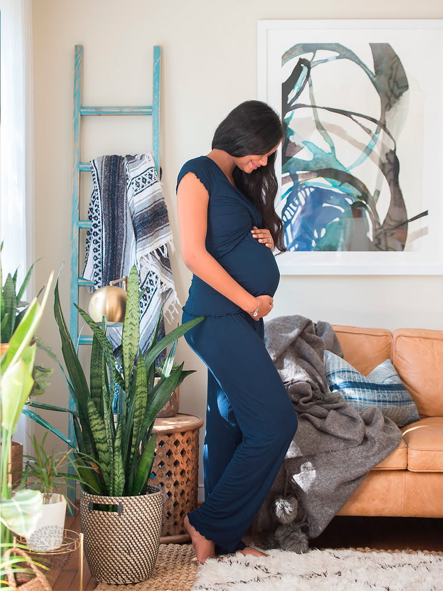 pregnant woman in a living room holding her belly wearing comfy blue nursing pajamas that are the perfect addition to a new mom care package