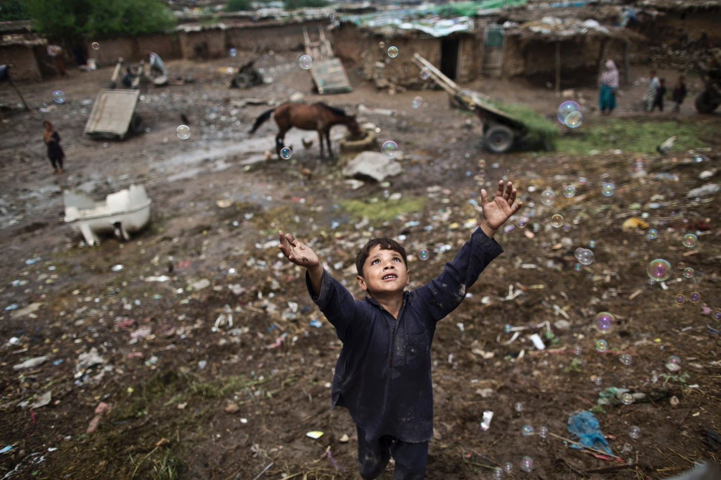 An Afghan refugee boy chases bubbles while playing on the outskirts of Islamabad, Pakistan