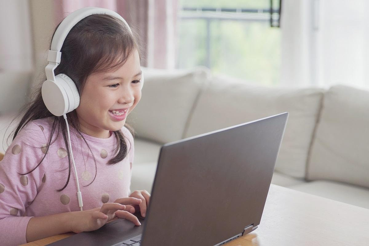 child wearing headphones and using laptop at home