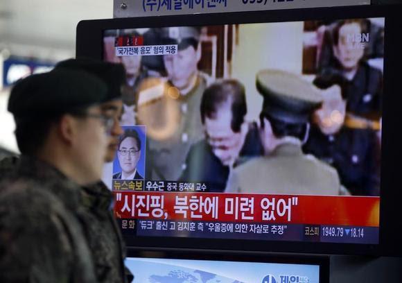 Soldados surcoreanos pasan junto a un televisor que muestra informes sobre la ejecución de Jang Song Thaek, quien es tío del líder norcoreano Kim Jong Un, en una estación de ferrocarril en Seoul 13 diciembre de 2013.  REUTERS / Kim Hong-Ji