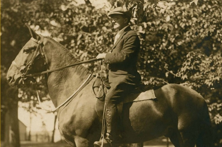 Sepia photo of a man wearing a paper boy hat riding a horse.