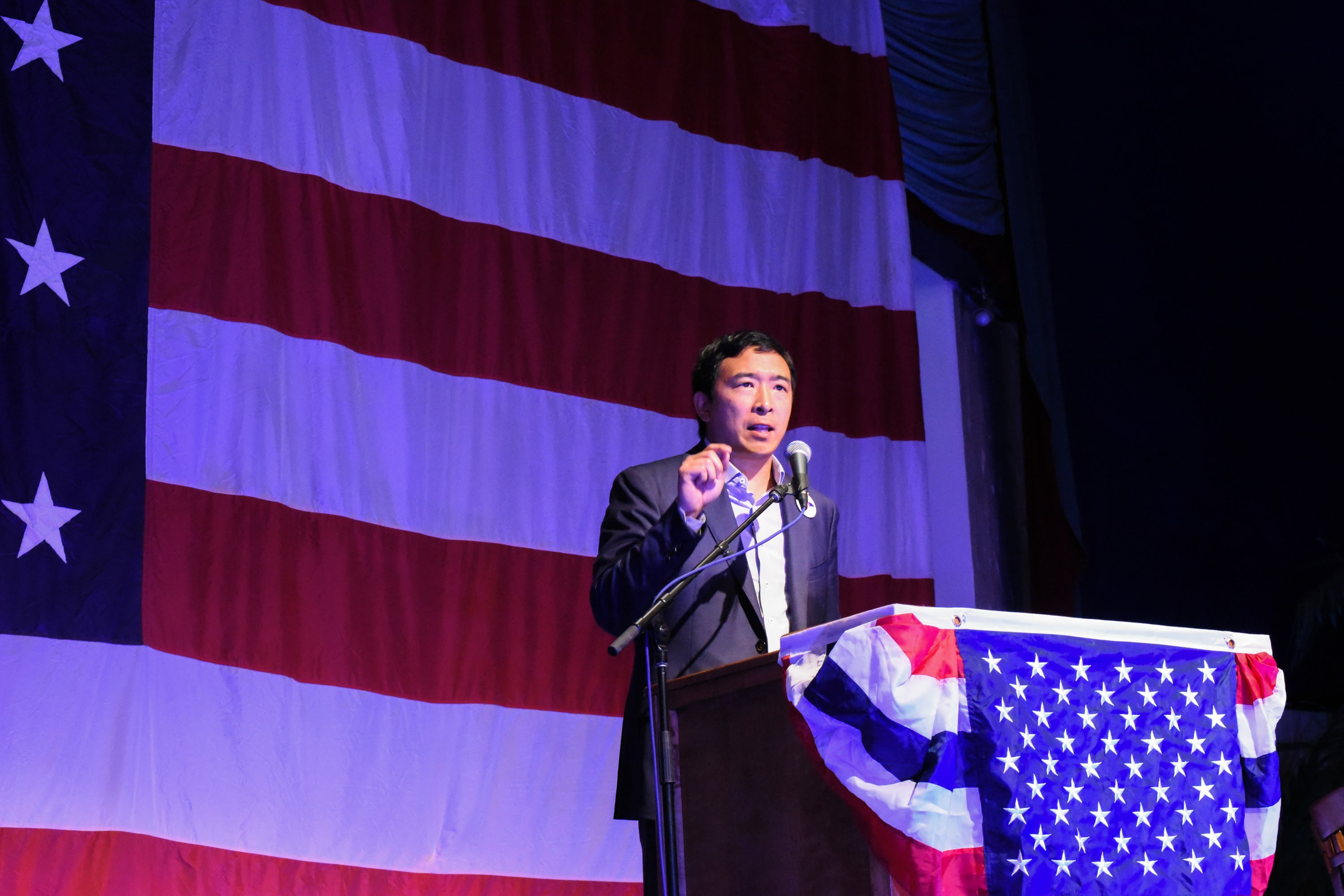 Andrew Yang at a lectern on a podium, delivering a speech to Democrat activists in Iowa