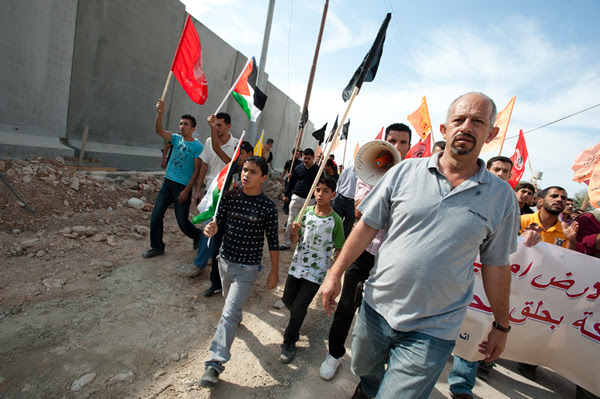 Jamal Juma' leads a nonviolent march against the Israeli separation wall in the West Bank town of Al-Walaja.