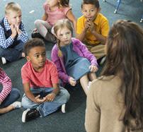 Teacher talking to small children.