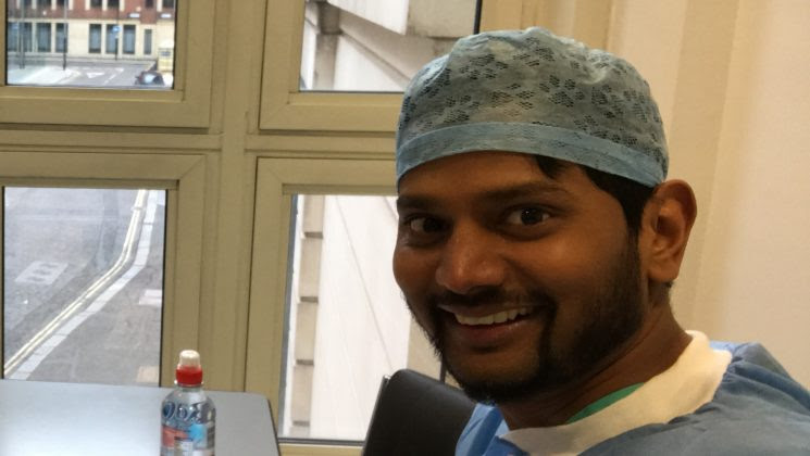 Image of Arun, an Indian NHS worker, in hospital scrubs