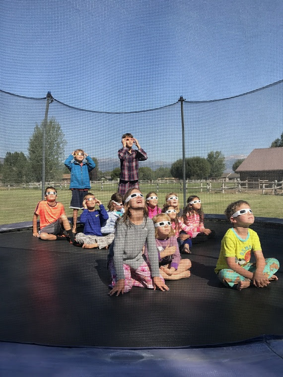A dozen children sit outside on a trampoline wearing eclipse safety glasses to watch the solar eclipse.