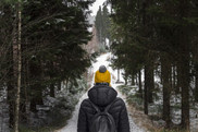 A woman hikes in the snowy woods wearing a yellow hat.