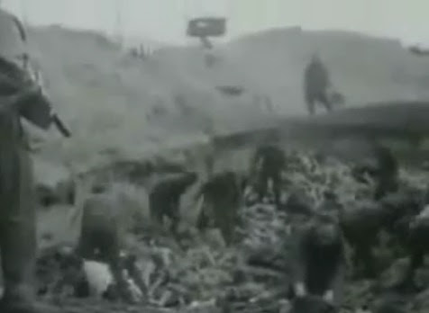 An SS group in a mass                             grave under the order of British machine                             guns (23min. 55sec.)