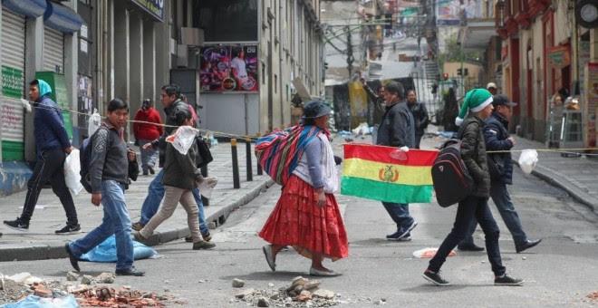 Gente paseando por las calles con una bandera de Bolivia. / EFE