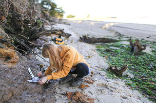 geology student taking records outside near a riverbed