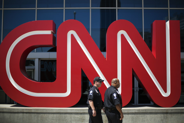 Security guards walk past the entrance to CNN headquarters in Atlanta. (David Goldman/AP)</p>