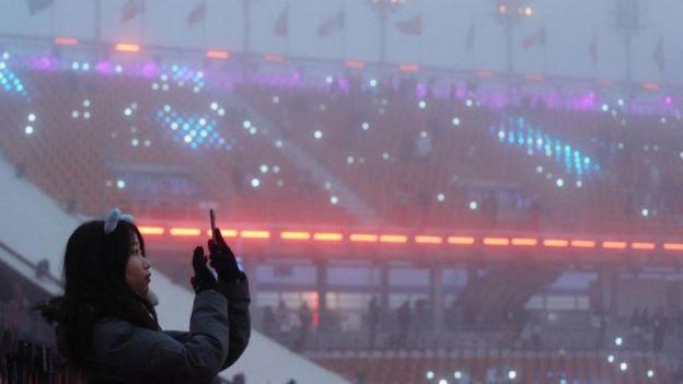 Moça tira foto com celular em estádio