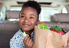 Girl in a car eats celery from a grocery bag.