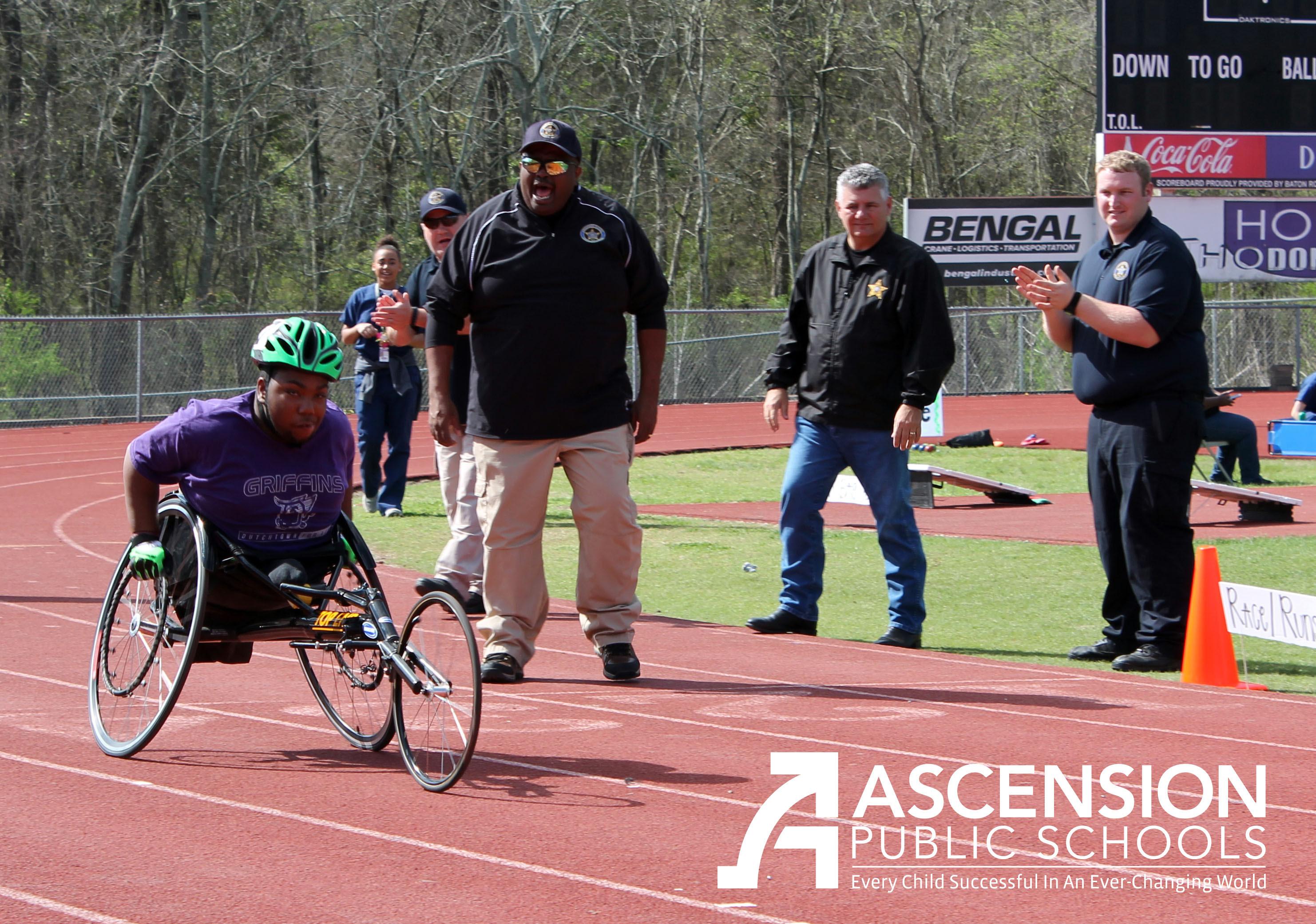 APSO staff cheer as K'Von races in his wheelchair