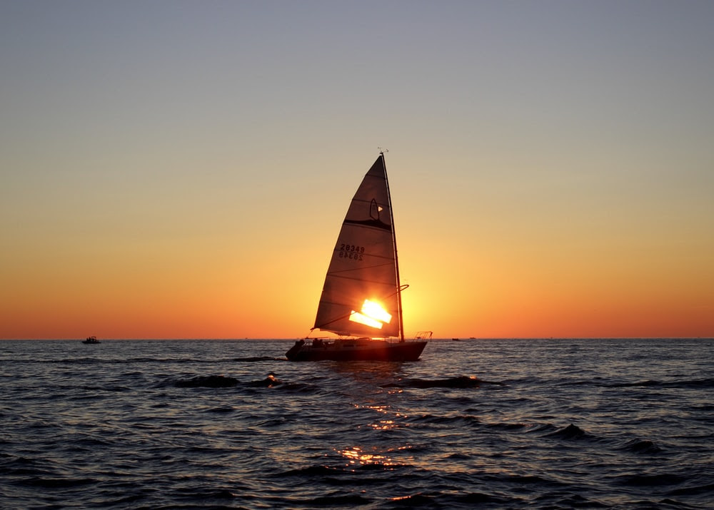Sailboat                                                           on the ocean                                                           at sunset