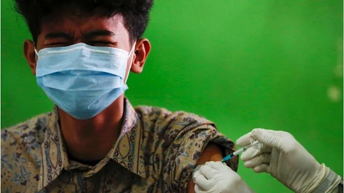 An Indonesian student reacts as he receives his first dose of China's Sinovac Biotech vaccine for the coronavirus disease (COVID-19) at a high school, as the cases surge in Jakarta, Indonesia, 1 July 2021.