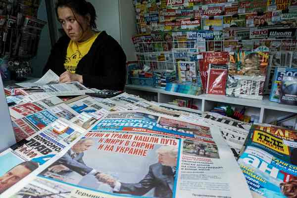 A woman browses in a Moscownewsstand among papers featuring PresidentTrump and Russian President Vladimir Putin on July 8. (KirillKudryatsev/Agence France-Presse via Getty Images)</p>