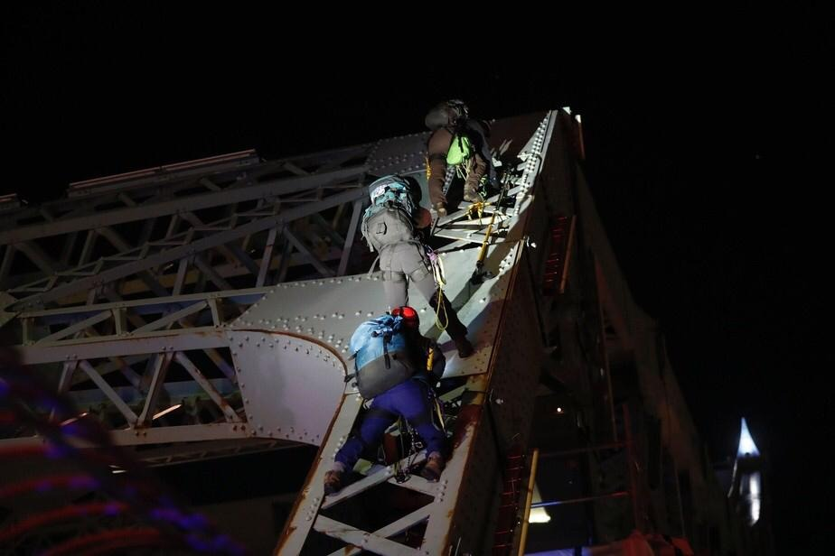 3 people abseiling down the side of a bridge at nighttime.