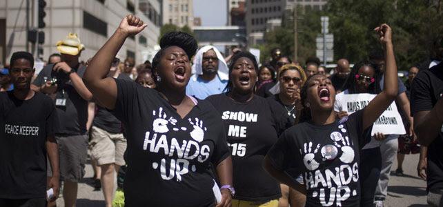 Manifestantes alzan sus puños mientras gritan proclamas pidiendo justicia para Brown en Ferguson