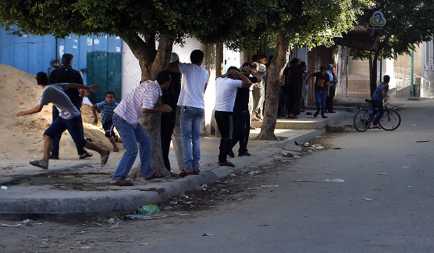 Palestinians take cover in a street in Gaza City, during an Israeli air strike.
