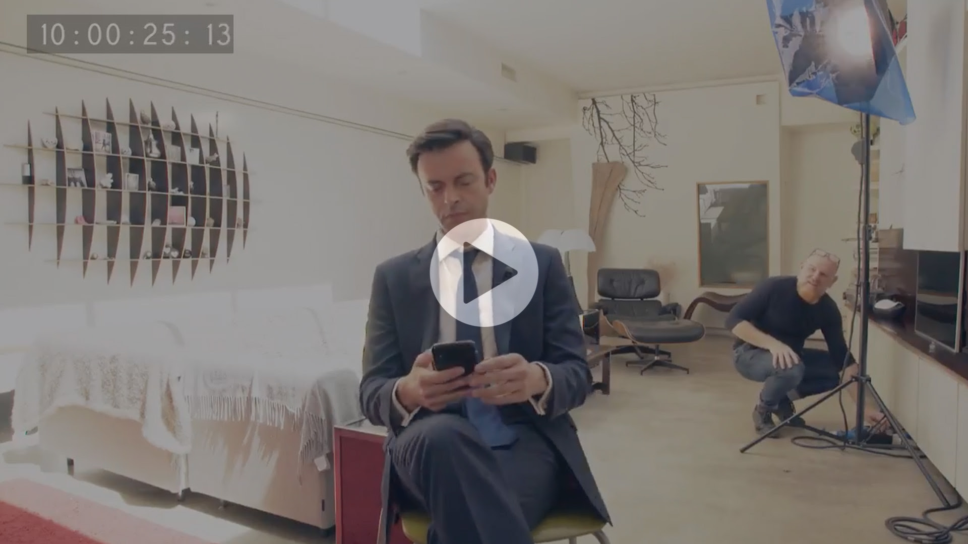 """Still from video, man with short brown hair sits in centre, wearing tie and blazer, looking at his phone, play button in centre"""""""