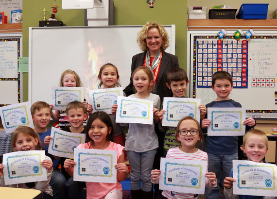 First-grade students hold up their Certificates of Completion for the Hour of Code with State Superintendent Jillian Balow.