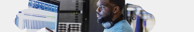 Homem usando PC: Homem negro com headphones olha monitor com gráficos.