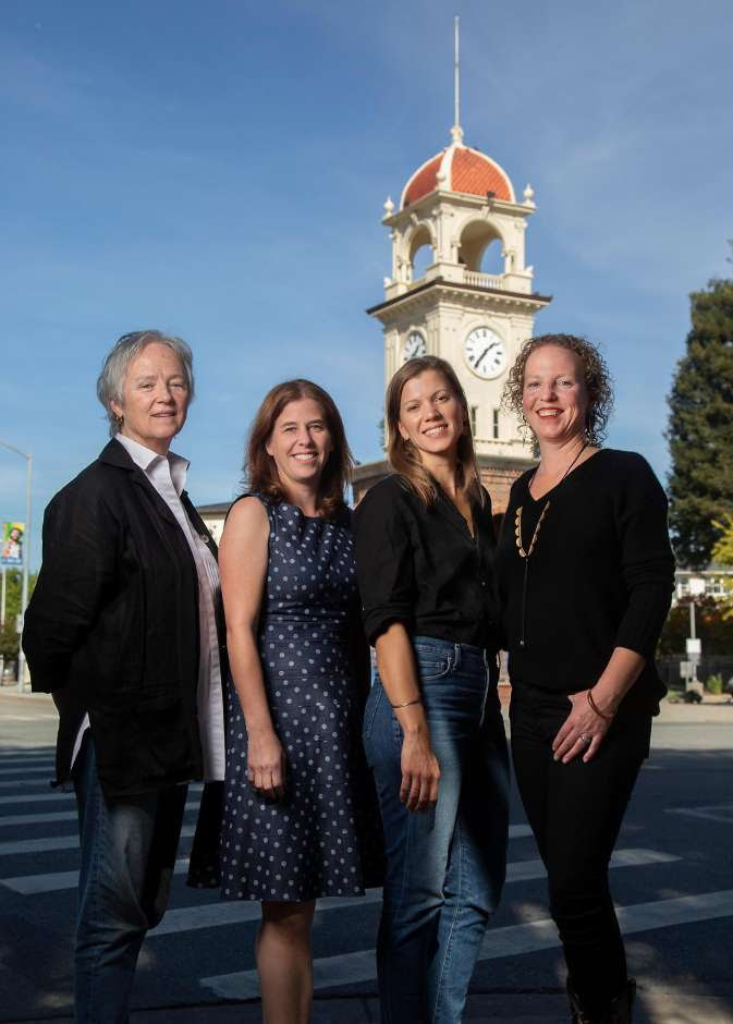 Four women pose together smiling at the camera in front of the Downtown Santa Cruz clock tower.