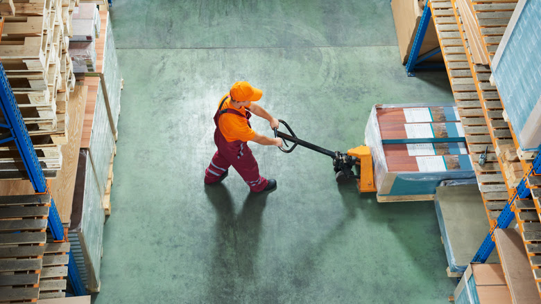 Worker with fork pallet truck stacker in warehouse loading furniture panels. © Dmitry Kalinovsky/ Shutterstock