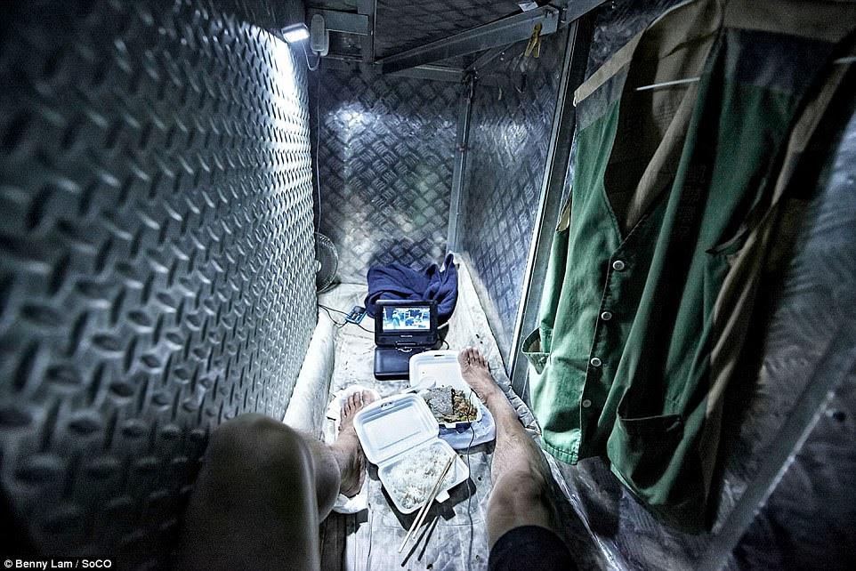 hình ảnh kinh hoàng này cho thấy một người thuê nhà ăn thức ăn trong một căn hộ chật hẹp bao quanh bởi những bức tường kim loại