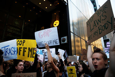 Protesters at Trump Tower in New York on Monday. Accusations against Donald J. Trump have led to questions about groping laws.