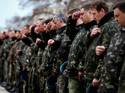 Soldados ucranianos de la base de Belbek, cerca de Simferópol, se santiguan tras rezar por la paz en una ceremonia religiosa. REUTERS/Thomas Peter